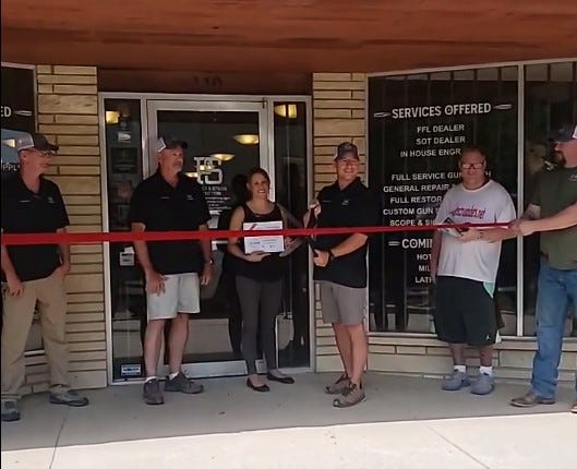 Powder and String Outfitters cutting Wellington Chamber ribbon in front of store on N. Washington Ave.