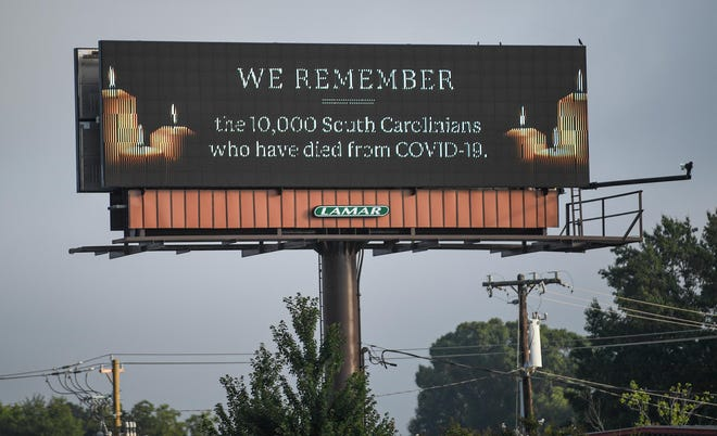 """A Lamar billboard on Clemson Boulevard in Anderson flashes """"We Remember the 10,000 South Carolinians who have died from COVID-19"""" in Anderson, S.C. Thursday, August 12, 2021."""