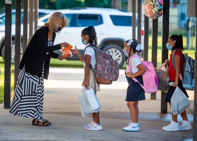 Kindergarten Asst Debra Pendley welcomes student as they arrive for the first day of school at Westside Elementary in Scott, LA. Thursday, Aug. 12, 2021.