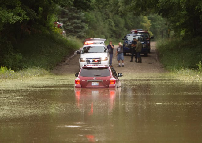 A Toyota Highlander is stuck in floodwater on Pingree Road near Jewell Road in Marion Township Thursday, Aug. 12, 2021.