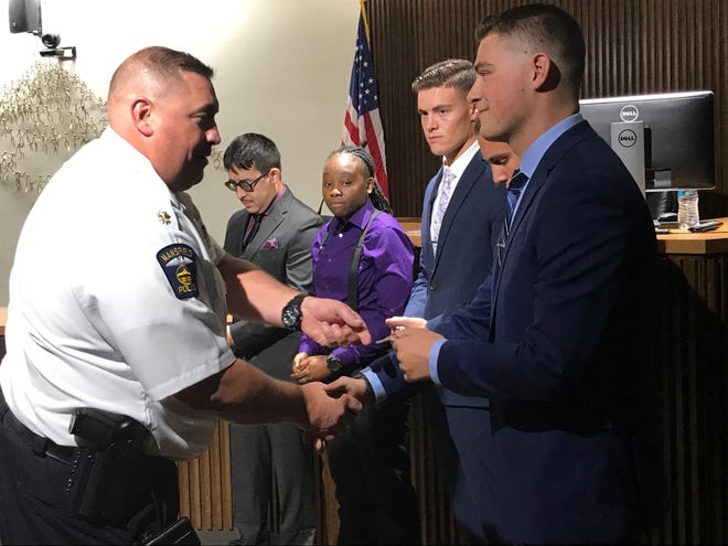 Assistant Mansfield police Chief Jason Bammann gives each new officer their badge Thursday during the swearing-in ceremony at Mansfield Council Chambers.