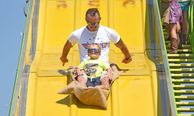 Maxton Brocwell, 2, holds on to father, Mason Brocwell, of Galion, as Mason pushes them down the slide at the Richland County Fair on Thursday.