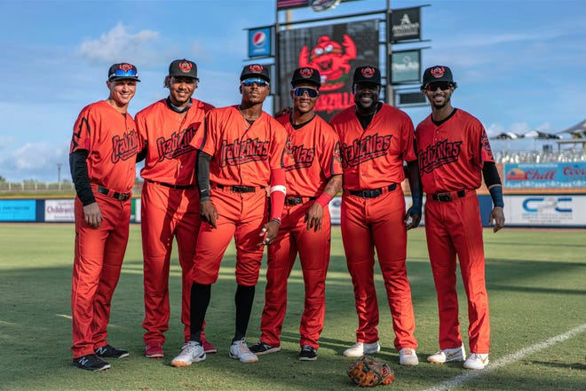 """Blue Wahoos players show off their one-night only """"Crabzilla"""" uniforms prior to their game against the Montgomery Biscuits on Aug. 11, 2021 from Blue Wahoos Stadium."""
