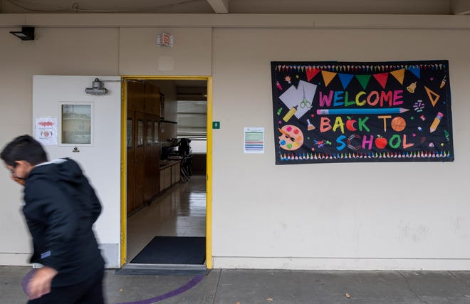A Natividad Elementary School student runs past a 'Welcome Back to School' sign hanging outside a classroom during the first day of school in Salinas, Calif., on Wednesday, Aug. 11, 2021.
