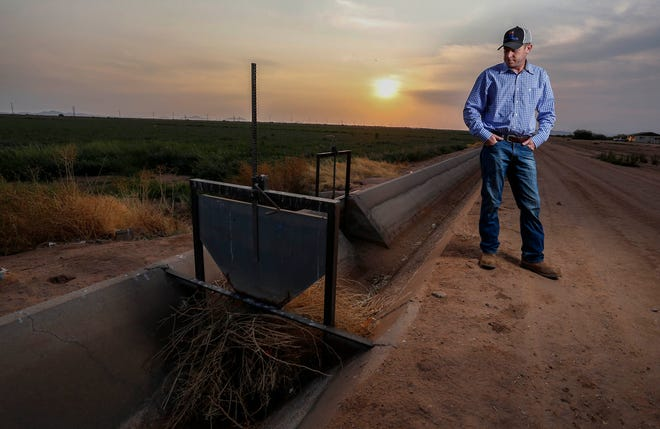 Will Thelander, a partner in his family's farming business, looks into a dry irrigation canal on his property, Thursday, July 22, 2021, in Casa Grande, Ariz.