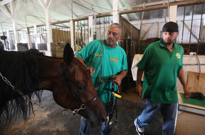 Lionel Watiker, left and his son Derek get a horse ready to train in the harness racing barn at the Muskingum County Fairgrounds on Thursday, Aug. 12, 2021. They're gearing up for the start of the 175th Muskingum County Fair, where Derek will drive races throughout the weekend.