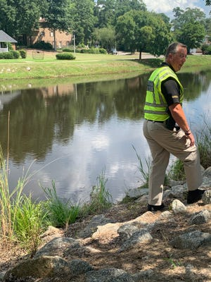 Richmond County Lieutenant Scott Redmon points out the disturbed rocks and reeds at the site where the car entered the pond.