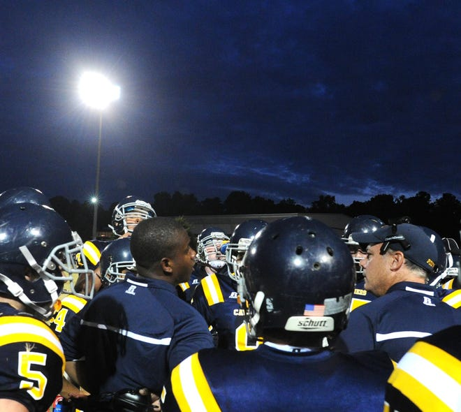 In this photo from 2012, Augusta Preparatory Day School coach Harry Bacheller (right) talks to his team during a time out against Thomas Jefferson Academy. The team was playing its first home game under lights.
