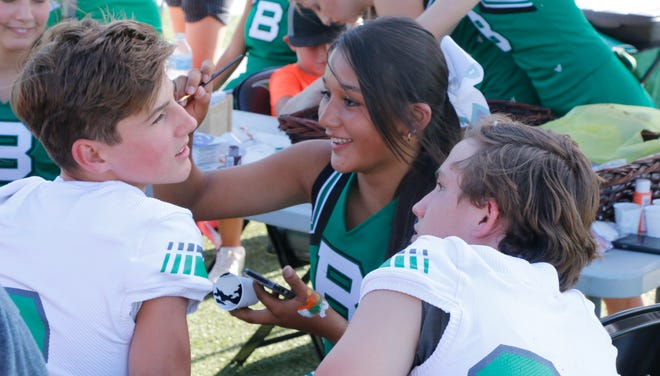 Bangs Dragons cheerleader Rylie Guerrero, a junior, paints the face of freshman football player Connor Loewrigkeit as Deavan Greaves, also a freshman, watches at Meet the Dragons Thursday evening at Dragon Memorial Stadium.
