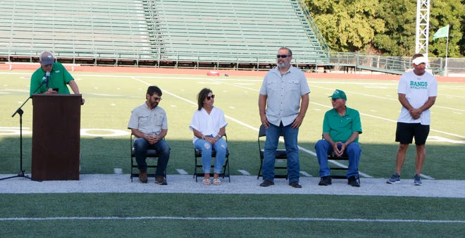 """Bangs school superintendent Dr. Josh Martin (at microphone) inducts the inaugural class of the Hall of Honor Thursday evening at Dragon Memorial Stadium. From left are Rick McClatchy and Holly Gieb, who were present on behalf of their late father, inductee Garner """"Dooder"""" McClatchy; and inductees Eric Cole and his father, David Cole. Bangs athletic director Kyle Maxfield stands at the right."""