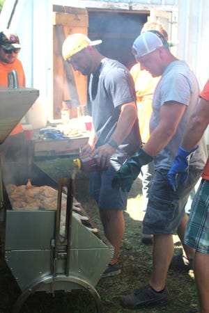Hundreds of halves of chickens were prepared in large roasters by members of the Topinabee Fire Department, including Jason and Josh Vieau, for their annual barbecue last year.