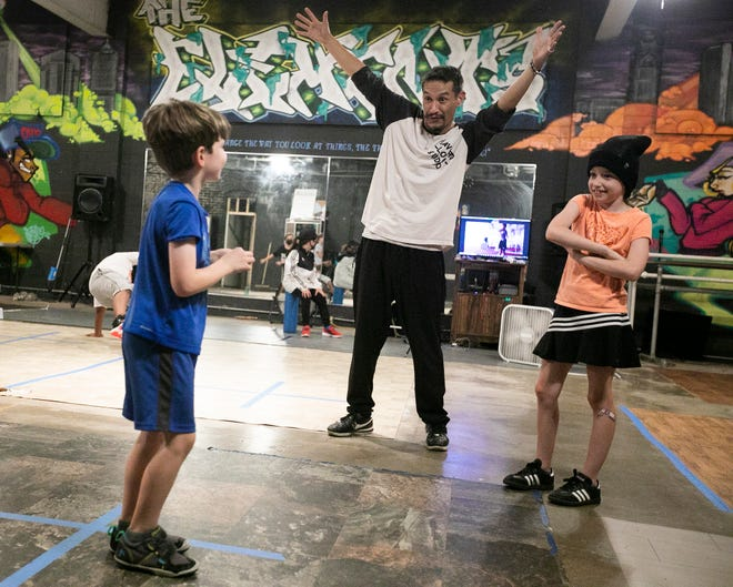 James Alexander, owner of Flavor'd Flow Studio, encourages, Jude Christy, 6, to try a bigger move during a break-dancing class on Columbus' South Side.