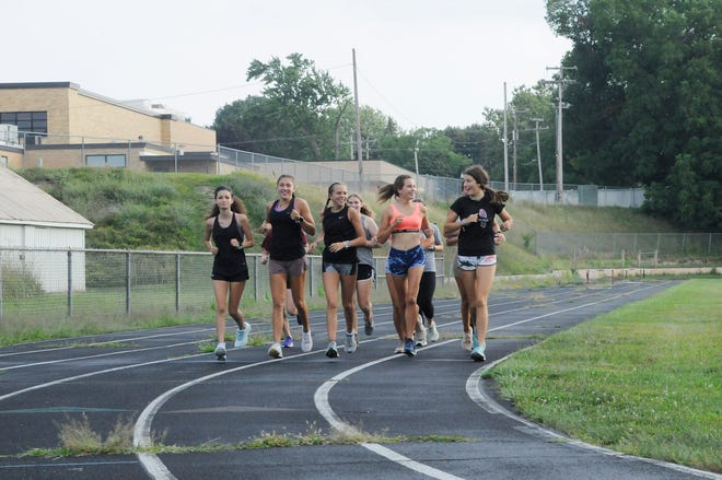 Tecumseh girls cross country team runs a warmup lap at the middle school track.