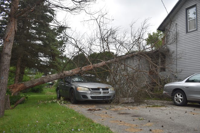 A tree, which snapped at its base, rests atop a car and a portion of this home on U.S. 233 near the Onsted Highway intersection. Lenawee County residents are still reeling for thunderstorms Wednesday and Thursday that caused damage such as this and power outages, many of which are expected to continue through the weekend.