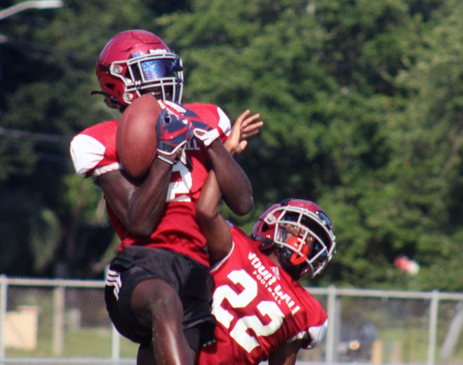 Raines' Kareem Burke (2) and Dequon King (22) go up for a jump ball in the end zone during high school football practice on August 11.