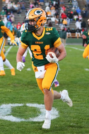 Crest's Carter Greene carries the football during its win over rival Burns last spring.
