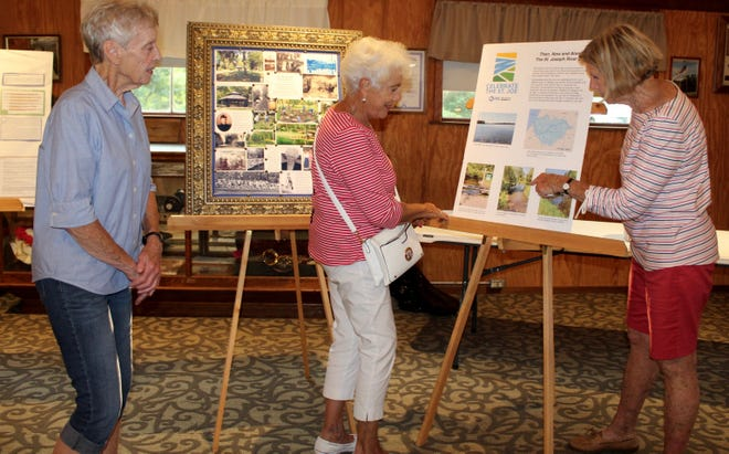 Hillsdale Historical Society member JoAnne Miller and Mrs. Stock's Park committee members Connie Erholtz and Louise Worms look at the display featuring St. Joseph River, made available during Tuesday night concerts at the park and at The Gospel Barn, in case of rain. [NANCY HASTINGS PHOTO]