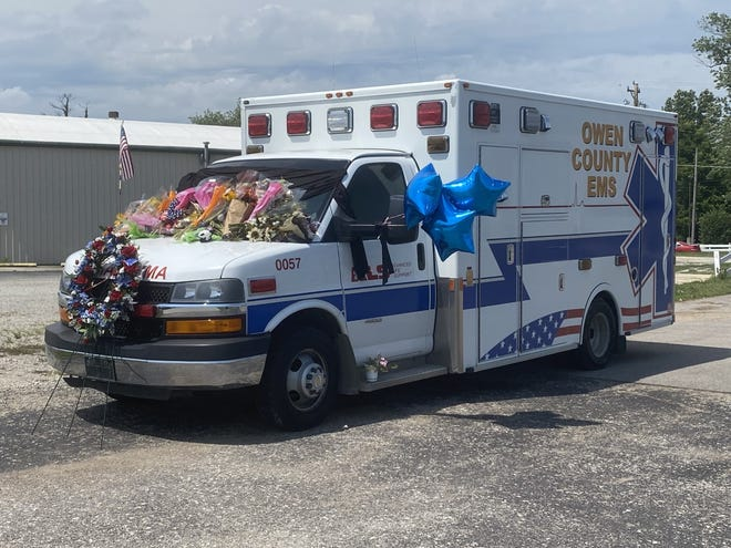 An ambulance laden with flowers and balloons  parked at the Owen County EMS office.