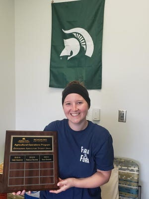 Grace Herkimer, shown here holding a plaque of award winners, is the recipient of the Outstanding Agriculture Student Award for 2021 at Monroe County Community College.