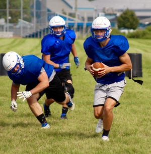 Dundee quarterback Carson Irwin (right) carries the ball during an offensive drill at practice Thursday, August 12, 2021.