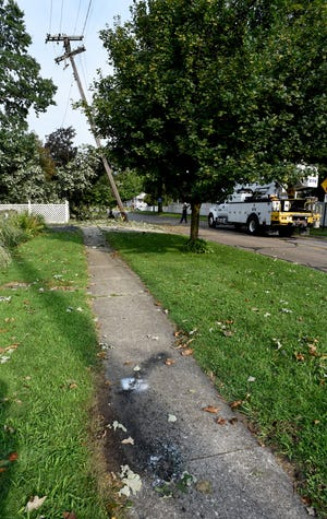 Evidence of a hot wire can be seen on the sidewalk outside Dan Stefanski's home following the storm Wednesday. Detroit Edison crews arrived around 9:30 a.m. Friday to asset the electrical pole leaning on E. Noble Ave. between Lincoln and S. Macomb Streets in Monroe.