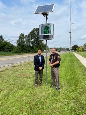Monroe County Sheriff Troy Goodnough (right) and Bedford Township Supervisor Paul Pirrone pose in front of one of the three new speed tracking signs that have been installed around downtown Lambertville. The project is a joint venture between the Bedford Township Downtown Development Authority, the Monroe County Sheriff's Office, and the Monroe County Road Commission.