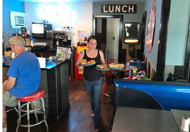 Scramblin' Rose server Sarah Hungerford brings out a tasty meal Aug. 13 for some appreciative patrons. The new diner is now open on Route 20 in Bouckville.