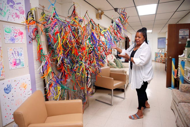 Clotiel Howard, founder and executive director of Hope for the Future, shows off the Tree of Life representing the children and their families that have come through the visitation center in Oklahoma City.