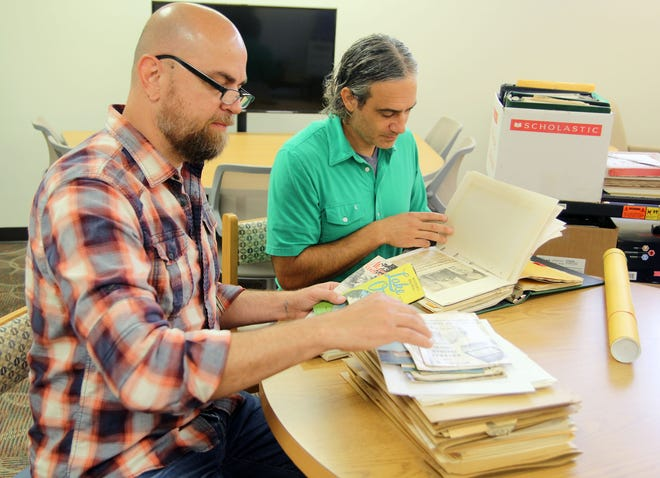 Missouri State University- West Plains faculty members Frank Priest, left, and Dr. Jason McCollom look through old brochures and newspaper clippings to determine if they meet the criteria for inclusion in the new Ozarks Heritage Resource Center at the Garnett Library. (MSU-WP Photo)