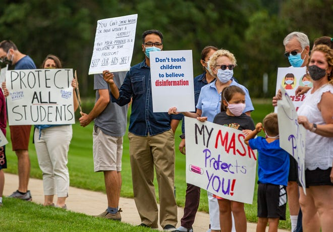 A group of residents hold signs in support of face mask safety measures outside the Penn-Harris-Madison School Corp.'s administration building on Friday in Mishawaka.