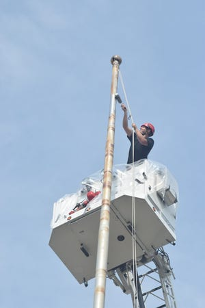 Off-duty Kewanee firefighters Kyle Bumphrey and Joel Rettiger went nearly 100 feet up in the fire department's aerial ladder truck Thursday to paint the flagpole, which had rusty spots. The pole was first installed in 1920 at the former Kewanee Boiler Co. plant and was moved in 2013 to Berrien Park in downtown Kewanee.