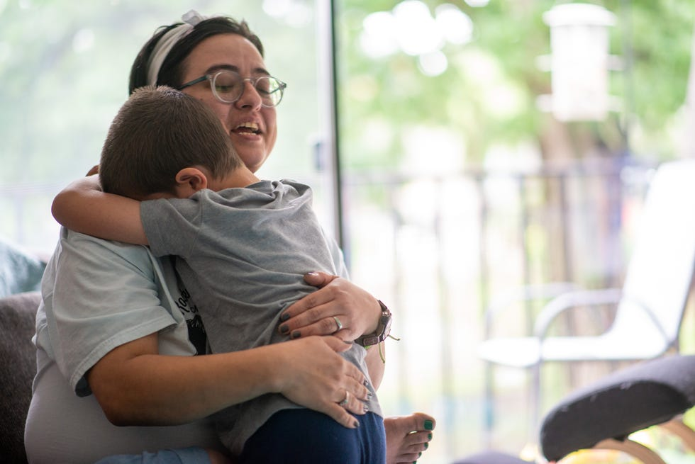 Mary Hammack, a resident of Trianon Apartments, hugs her 6-year-old son, Decklan, earlier this summer inside their apartment. Hammack said unresolved maintenance issues at Trianon have affected various aspects of their daily lives.