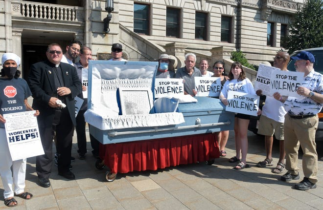 """Pastor Mike Stoliker of the Field of Dreams Ministries, second from left, joins with members of Worcester's """"Stop the Violence"""" advocacy group Thursday in front of City Hall to remind citizens that anyone could be the next person inside a coffin if violence in the city is not stopped."""