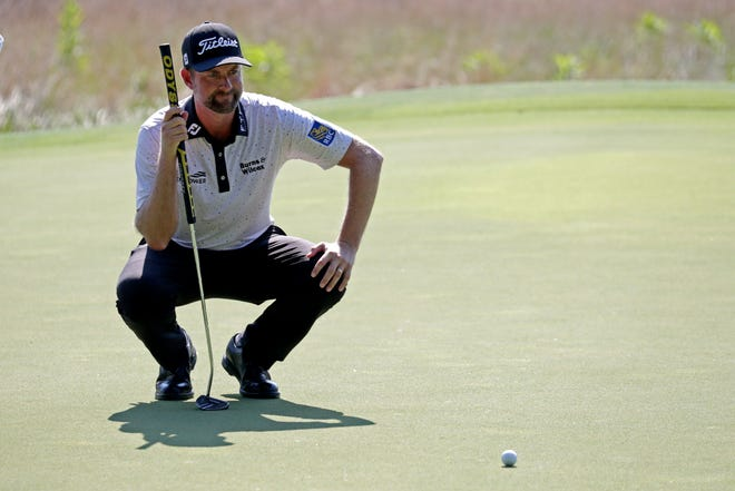 Webb Simpson looks over a putt on the first hole, the 10th hole he played during Friday's second round of the Wyndham Championship at Sedgefield Country Club.