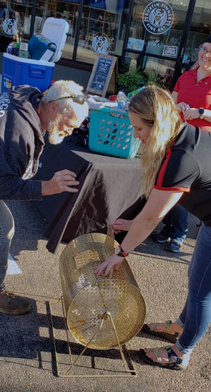 Emily Hagge helps a raffle player put his name into the basket during Thursday Night Live in Watertown.