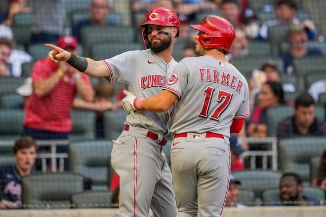 Aug 12, 2021; Cumberland, Georgia, USA; Cincinnati Reds shortstop Kyle Farmer (17) reacts with left fielder Jesse Winker (left) after hitting a two-run home run against the Atlanta Braves during the sixth inning at Truist Park. Mandatory Credit: Dale Zanine-USA TODAY Sports