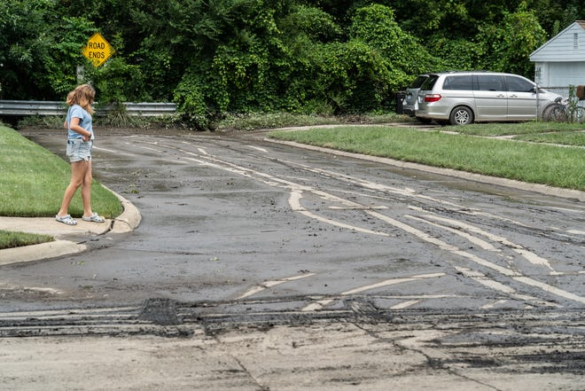 Maddie George of Dearborn Heights looks over leftover sewage water at the intersection of Hanover Street and Banner Street near her home in Dearborn Heights on Friday, August 13, 2021 after flood waters receded.