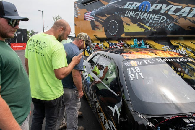 A group of workers check out the TC2 Motorsports drag racer during a press preview event for the Roadkill Nights Powered by Dodge drag race on Friday, Aug. 13, 2021.