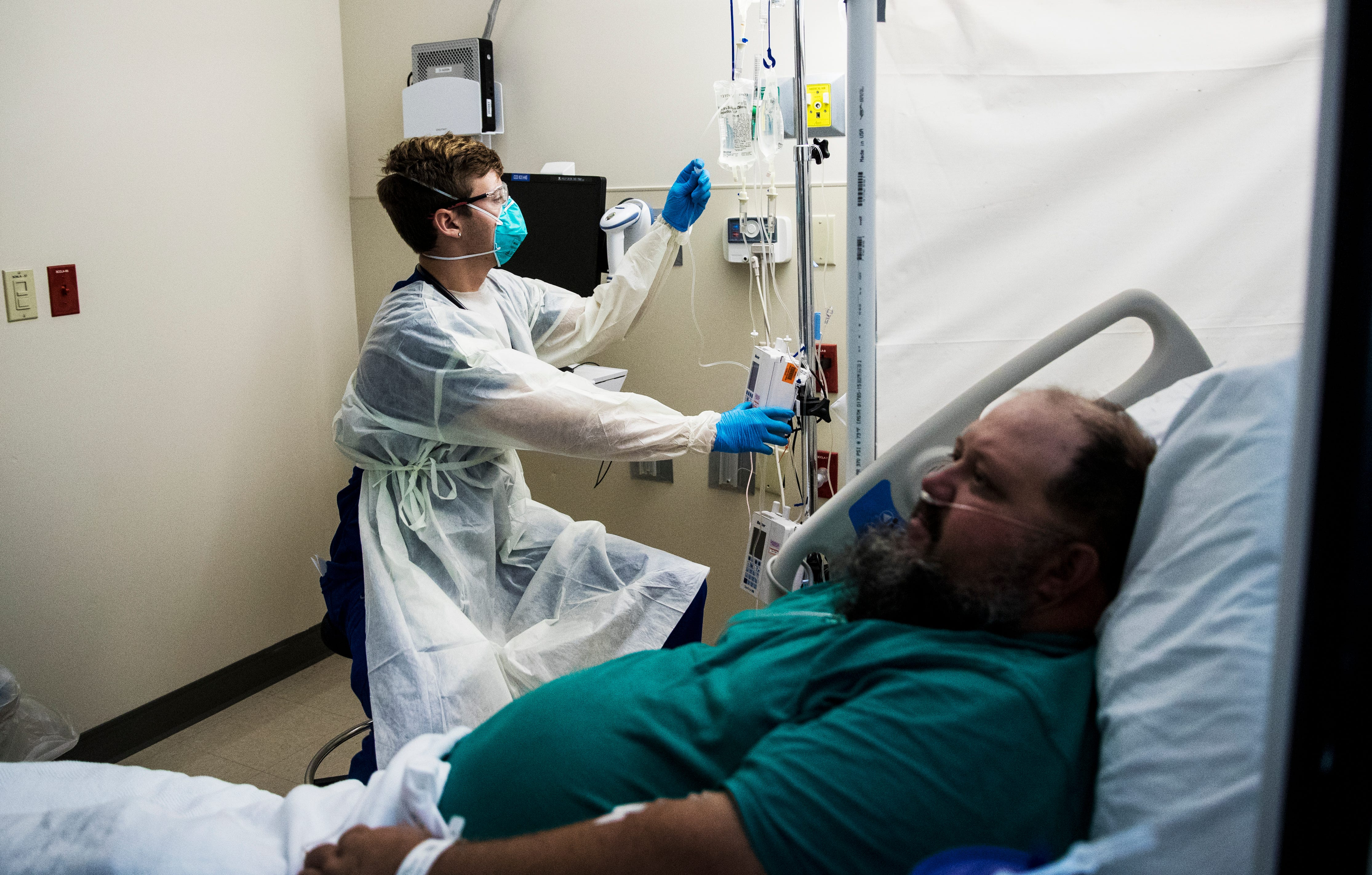 Matthew Josephson, a registered nurse at Gulf Coast Medical Center, treats Aaron Renfroe for symptoms associated with COVID-19 on Friday, Aug. 13, 2021. Renfroe, who is unvaccinated, tested positive for COVID-19 along with his family. He said his wife is also in the hospital with COVID-19.