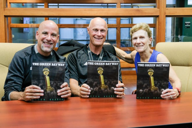 """UWGB women's head coaches past and present, from left, Matt Bollant, Kevin Borseth and Carol Hammerle recently autographed copies of """"The Green Bay Way,"""" written by Peter Kraker, the father of past great Mehryn Kraker."""