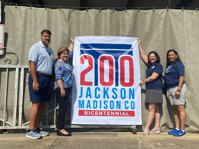 Bicentennial Commission members Jack Matthis, Judy Renshaw, Elaine Christian and Sabrina Anderson show one of the banners that will be hanging at the Bicentennial Kickoff celebration on Saturday in Downtown Jackson.
