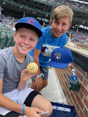 Yakir Schwartz (left) and Micah Schechter show off a ball signed by Manny Piña after the Brewers beat the Cubs on Thursday.