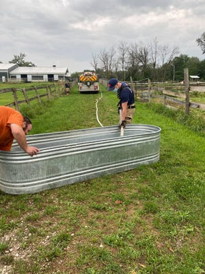 Two firefighters fill troughs with water at Miller Equestrian Center during a power outage on Aug. 11.