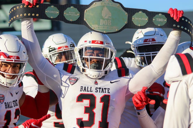 """Ball State linebacker Anthony Ekpe holds up a """"Detroit or Bust"""" belt during a game for the Cardinals in 2020."""