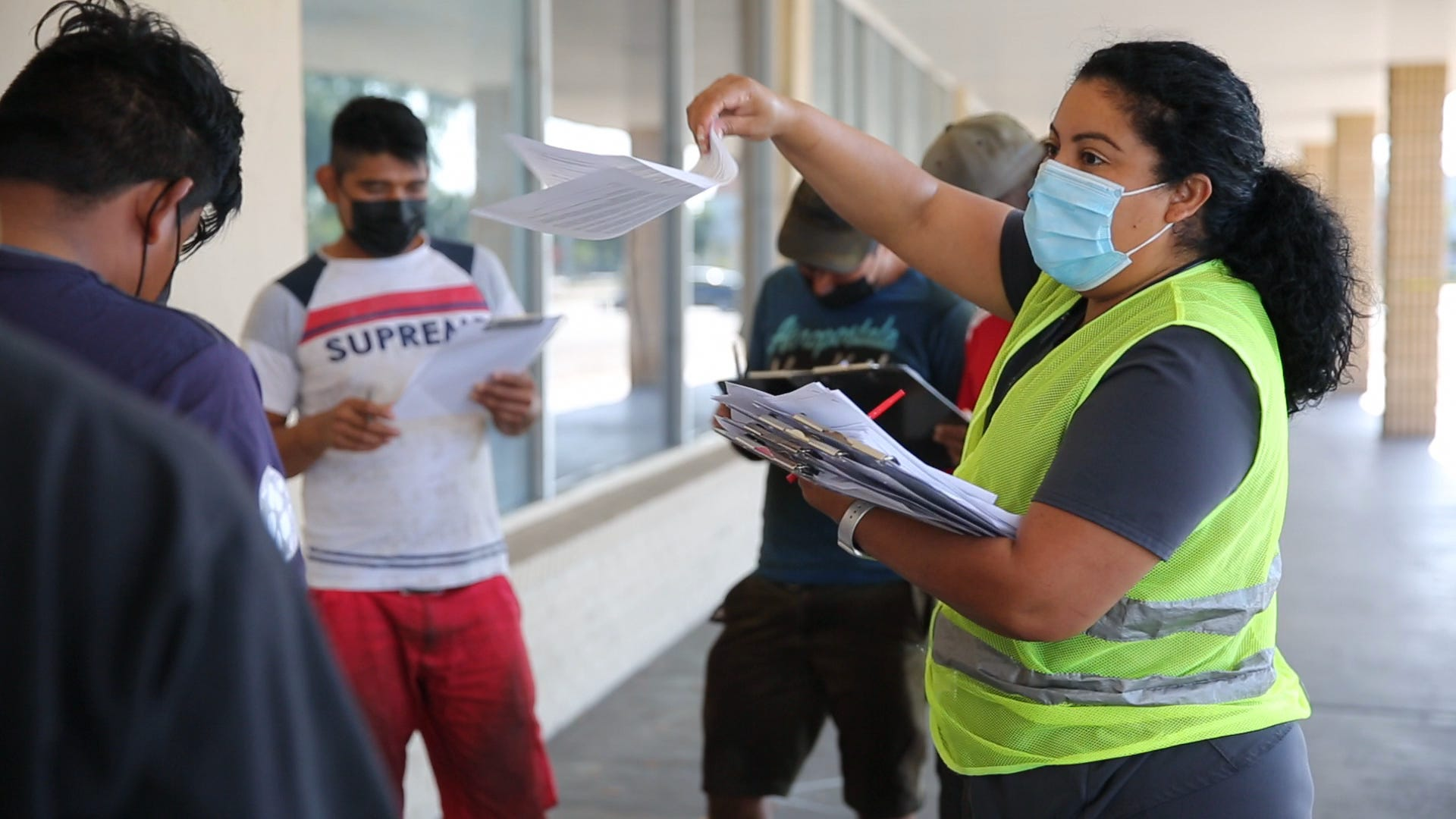 Midania Hinojosa helps a group of farmworkers with their paperwork while they wait in line during a vaccine clinic for farmworkers at the Florida Department of Health in Collier County site on Lake Trafford Road in Immokalee on Saturday, April 10, 2021.