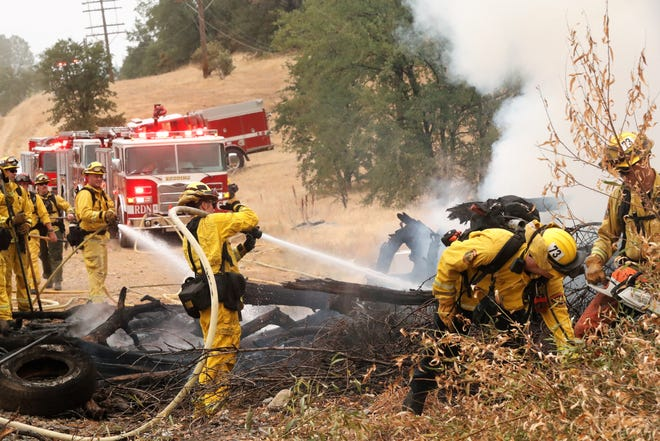 Firefighters extinguish a fire in a pile of branches, tires and other rubbish next to the train tracks off Oasis Road between Alee Lane and the Redding STEM Academy on Friday morning, Aug. 13, 2021. The fire sent up a dark plume of smoke from its north Redding location that could be seen against a backdrop of forest fire smoke in the distance.