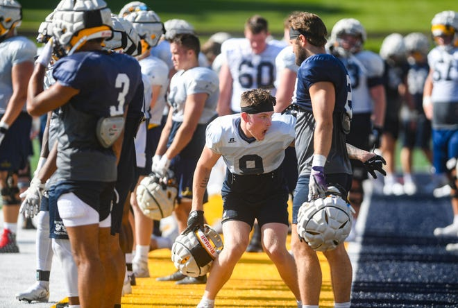 Running back Jarod Epperson jokes with a teammate on the sidelines during Augustana football practice on Friday, August 13, 2021 at Kirkeby-Over Stadium in Sioux Falls.