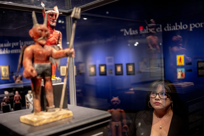 Erica Marin, the director at the El Paso Museum of History, looks at devil effigies from The Devil You Say! exhibition.