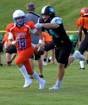Oak Grove linebacker Collin Frank pursues Randleman quarterback Christian Long during their scrimmage on Friday at Simeon Stadium. [Mike Duprez/USA Today Network]