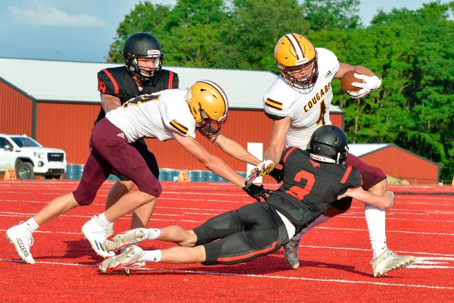 Bloomington North's Aidan Steinfeldt (4) runs upfield after making a catch as Edgewood's A.J. Sherfick (3) closes in to make the tackle during Friday night's scrimmage in Ellettsville.